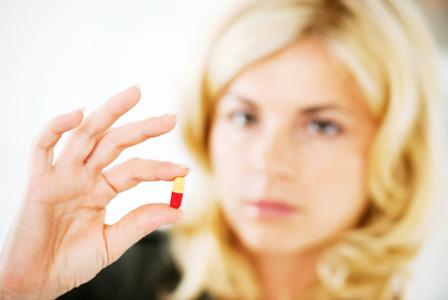 woman-holding-diet-pill-horiz